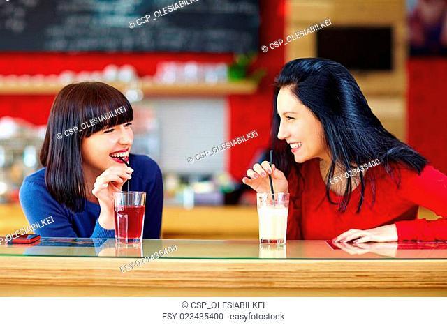 happy girls drink beverages in bar