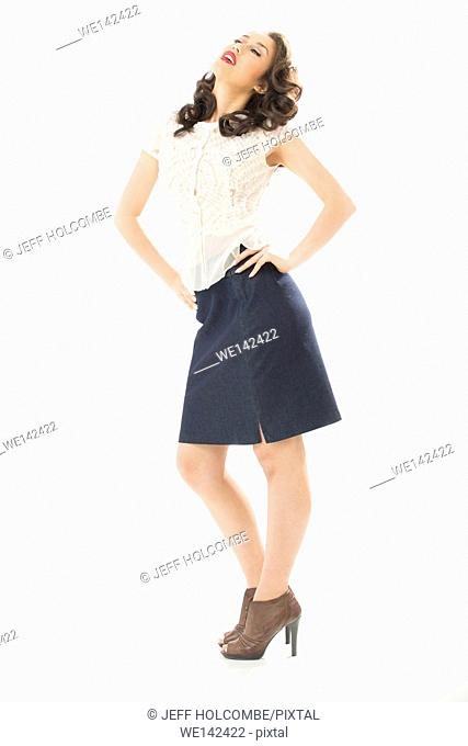 Beautiful young woman in white blouse and blue denim skirt, full length in brown heels, hands on hips, head thrown back