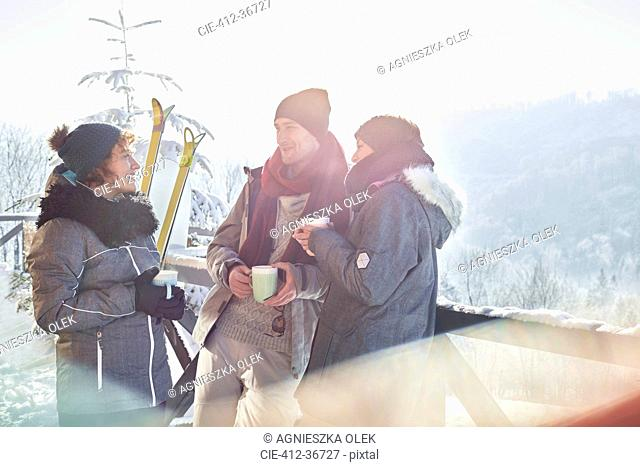 Skier friends talking, drinking coffee and hot cocoa apres-ski