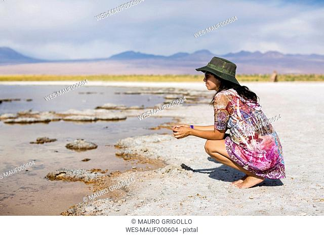 Chile, San Pedro de Atacama, woman crouching in the desert at lakeside