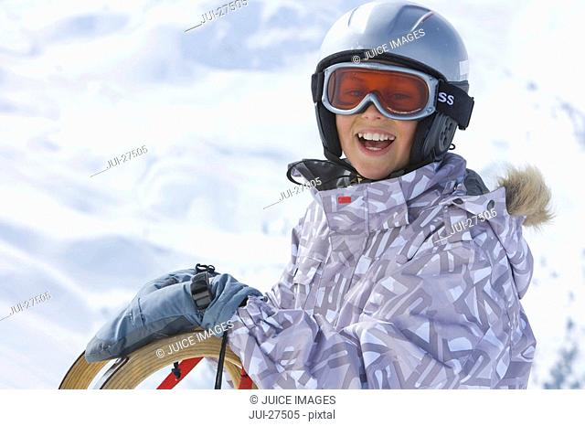 Smiling boy standing in snow with sled