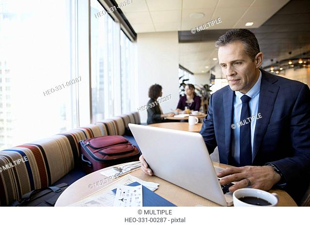 Businesswoman using laptop and drinking coffee in airport lounge