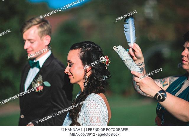 Alternate bridal couple at spiritual wedding ceremony outdoors, ceremony, feather, half portrait