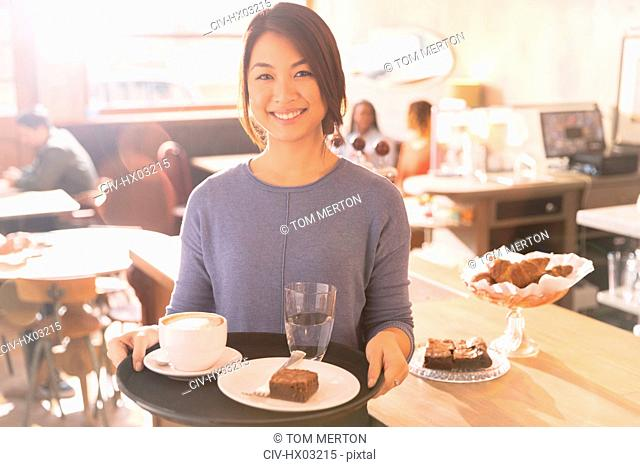Portrait smiling waitress carrying tray with cappuccino, brownie and water in cafe