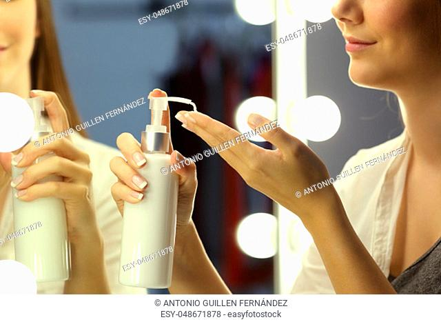 Portrait of a woman applying moisturizer cream on hands in front of a make up mirror