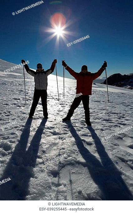 Silhouette couple raising hands with ski poles on snow covered landscape against clear blue sky