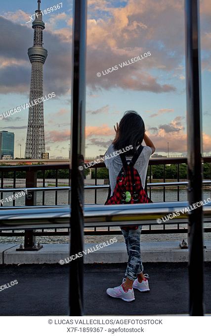 Girl taking pictures Sky Tree from Sumidagawa river, Asakusa District, Tokyo, Japan
