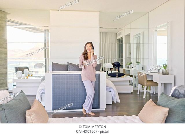 Woman talking on cell phone in modern luxury home showcase bedroom