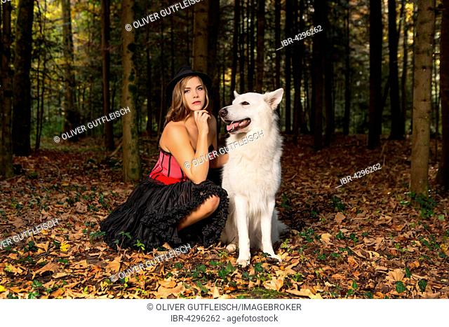 Blonde woman with white shepherd dog in the forest