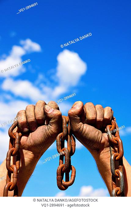 Two men's hands in the mud hold a rusty metal chain against the sky