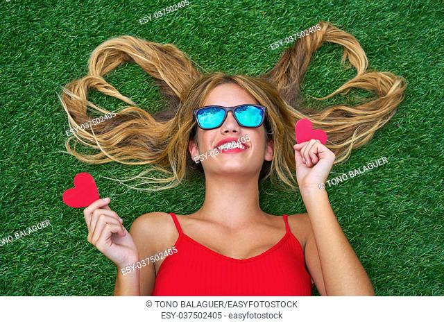 Blond teen girl with hair heart shapes lying down on turf