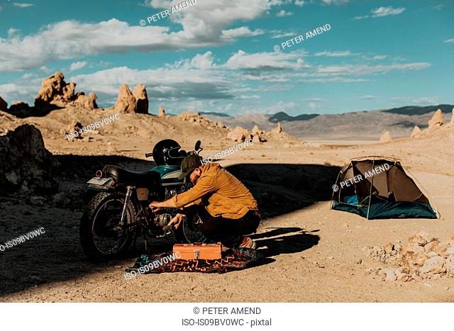 Motorcyclist fixing bike beside tent, Trona Pinnacles, California, US