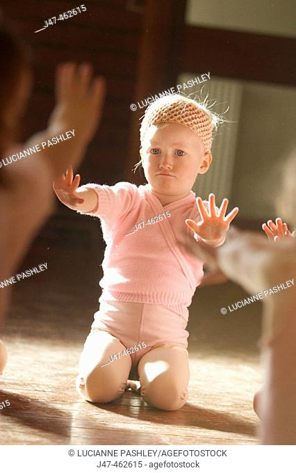 A 3 year old  girl in a ballet class, dressed in pink leotards and tights, stretching her arms out to say no