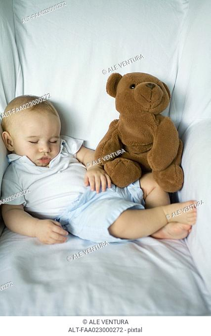 Baby sleeping in arm chair with teddy bear, portrait
