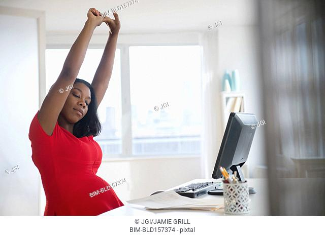 Black pregnant businesswoman stretching arms at desk in office