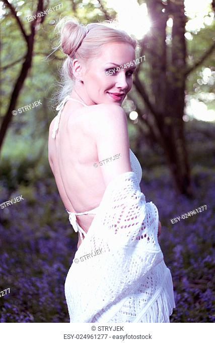 Artistic portrait of a girl in a bluebell forest