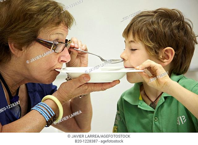 Grandma and grandson eating from the same dish, tasting session in sensory analysis lab, AZTI-Tecnalia Marine and Food Research Center, Derio, Bizkaia, Euskadi