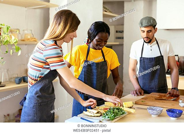 Friends preparing pineapple in kitchen