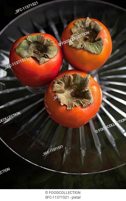 Three persimmon on a glass stand