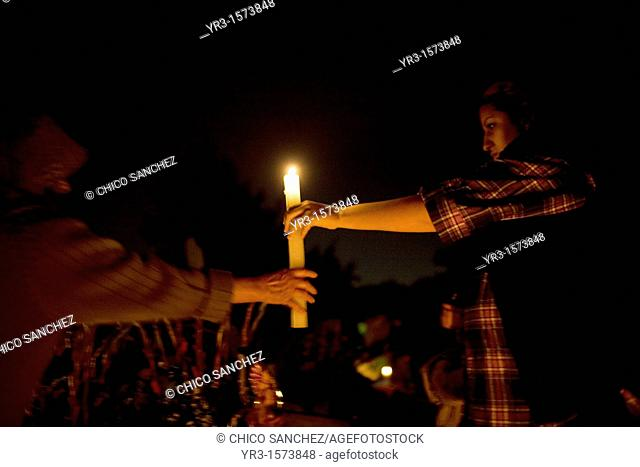Women pass a candle as they decorate the grave of a family member at the cemetery in San Gregorio Atlapulco, Xochimilco, Mexico City