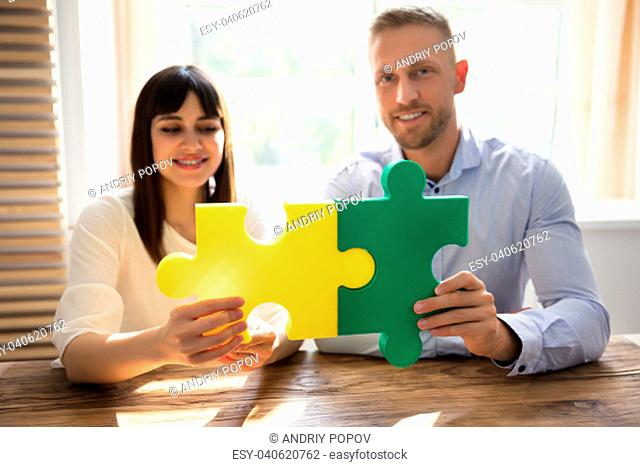 Two Happy Businesspeople Joining Green And Yellow Colored Jigsaw Pieces