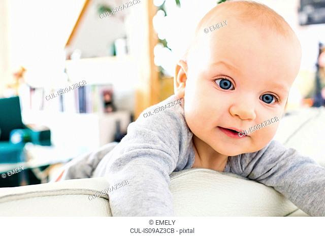 Blue eyed baby girl climbing on sofa