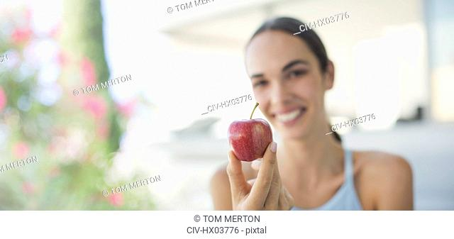 Portrait smiling brunette woman holding red apple