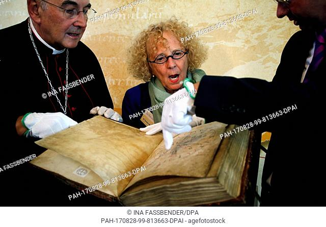 The former owner, Sandra Hindman (r) from the US, and Bishop Felix Genn look at the Liesborn Evangelion ('Liesborner Evangeliar') during its official...