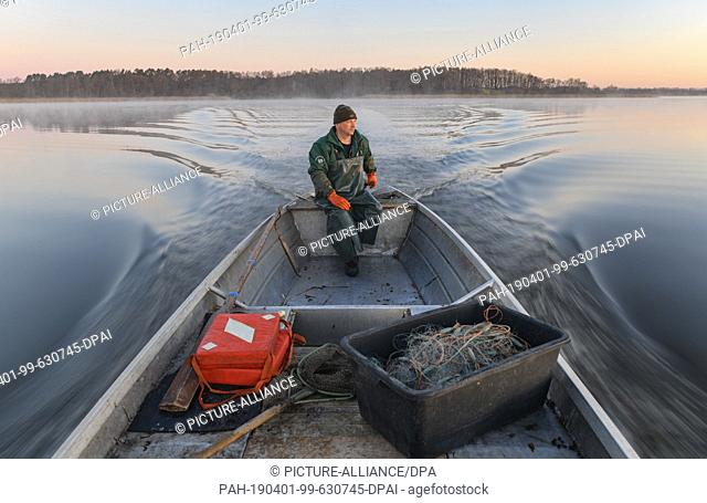 01 April 2019, Brandenburg, Groß Schauen: Laszlo Acz, fisherman of the fishery Köllnitz, goes in the early morning to the sunrise with his barge over the Groß...