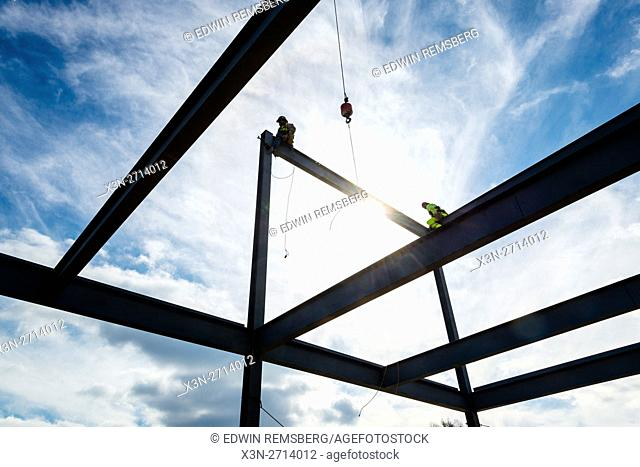 Iron workers sitting on a beam at a construction site
