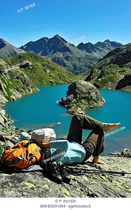female mountain wanderer resting at Bellacomba lake, Italy, Val d'Aosta