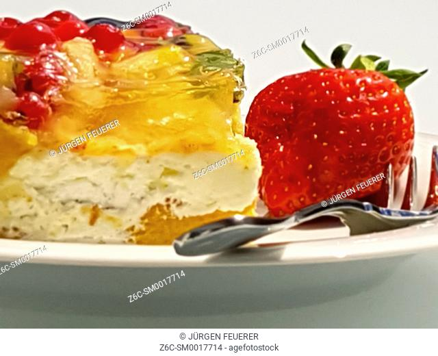 piece of colorful fruit cake with layers and strawberry