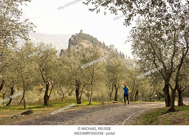 Italy, Mature man jogging on trail
