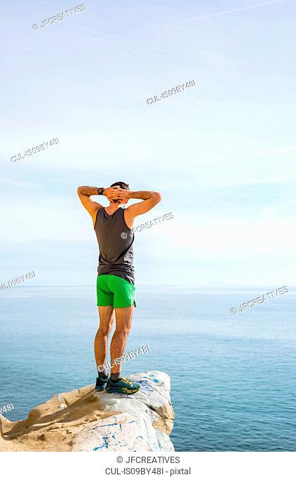Runner looking out at sea on protruding rock, Santa Barbara, California, USA