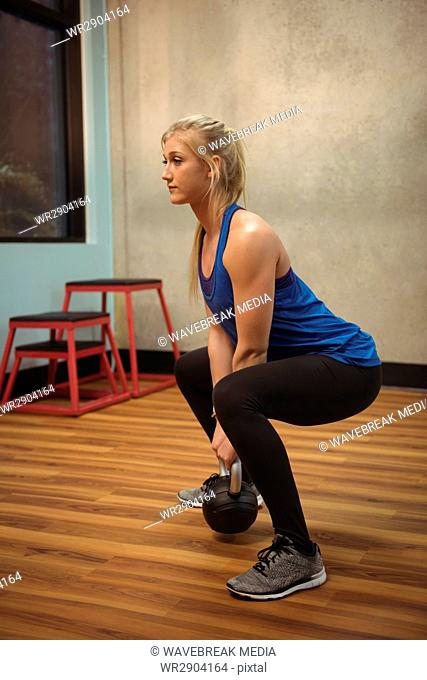 Fit woman exercising with kettlebell