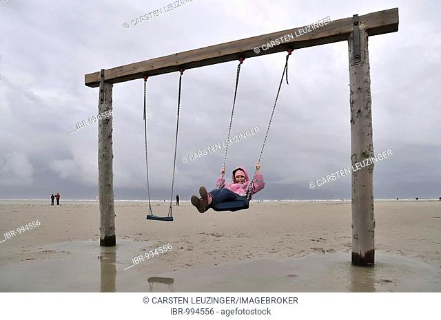 Young girl, 6 years old, on a swing at the beach in St. Peter-Ording, Eiderstedt Peninsula, Schleswig-Holstein, Germany, Europe