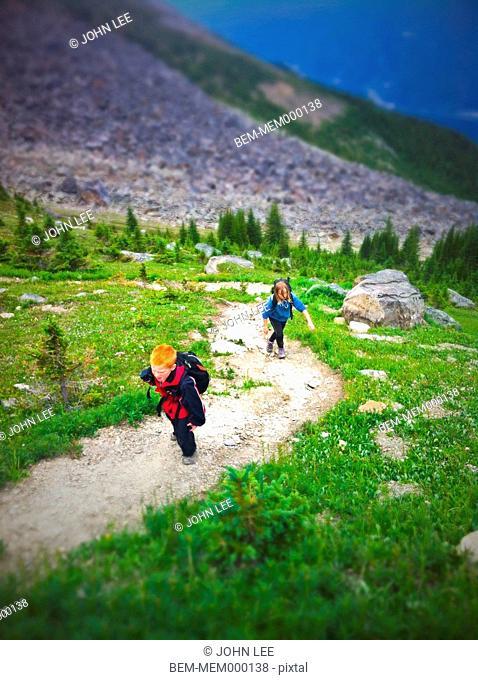 Caucasian children climbing up mountain path, Jasper, Alberta, Canada