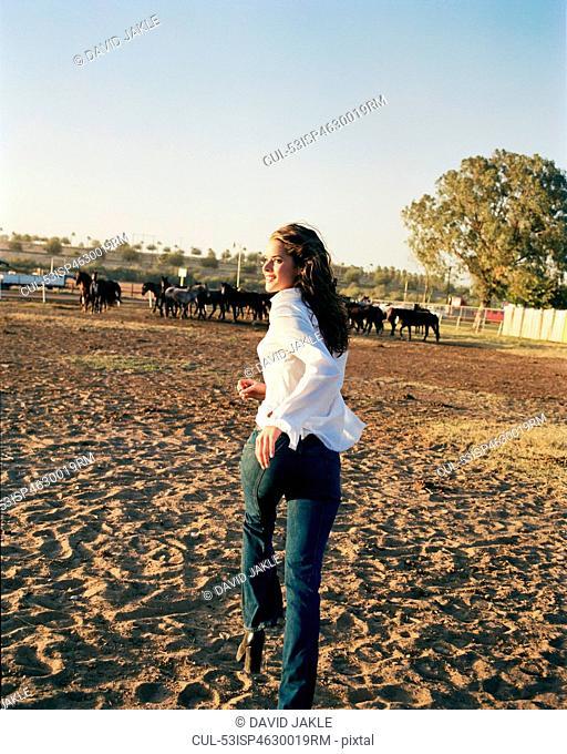 Woman walking in horse pen