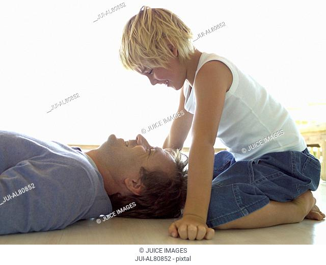 Father laying on floor with son sitting over him
