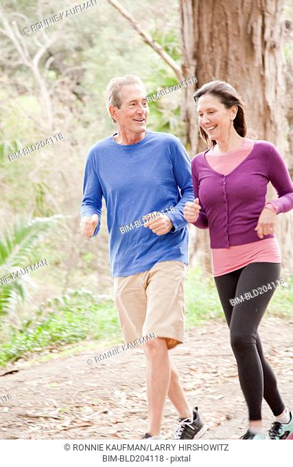 Older Caucasian couple jogging in forest
