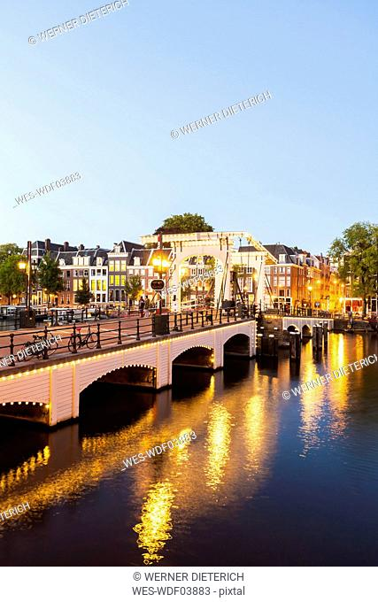 Netherlands, Amsterdam, view to Magere Brug with Amstel River in the foreground at evening twilight