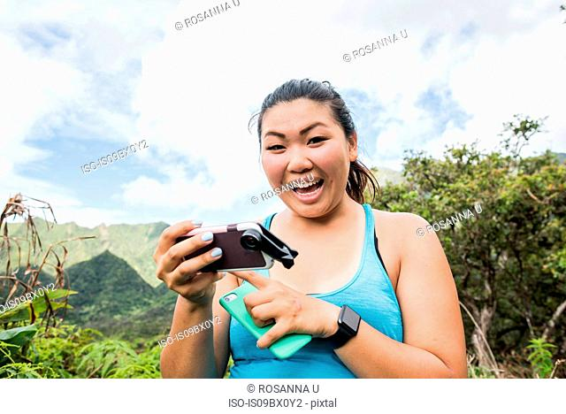 Hiker with cellphones in rainforest, Iao Valley, Maui, Hawaii