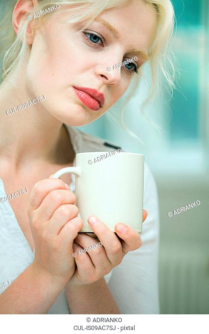 Wistful looking young woman with a coffee