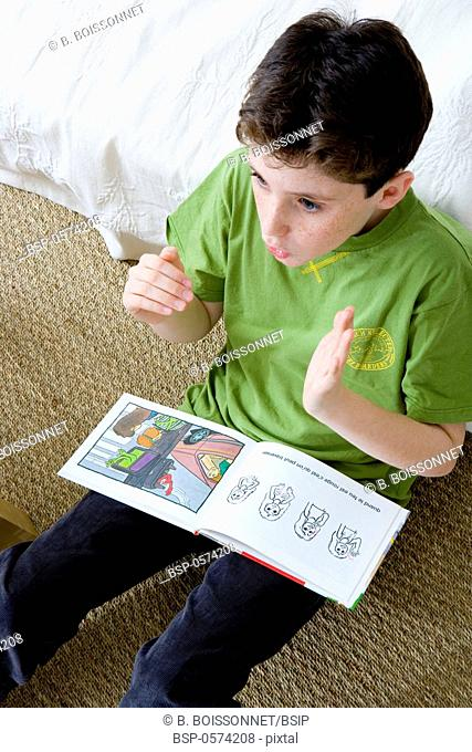 SIGN LANGUAGE Model. Do not use for HIV. A young boy reading a book presenting the dangers to avoid in daily life; the illustrations are accompanied of written...