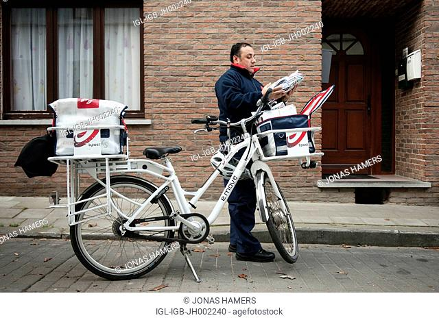 Picture shows belgian postman with his bicycle as he delivers a certified mail / letters / packages during his daily round circuit in the streets