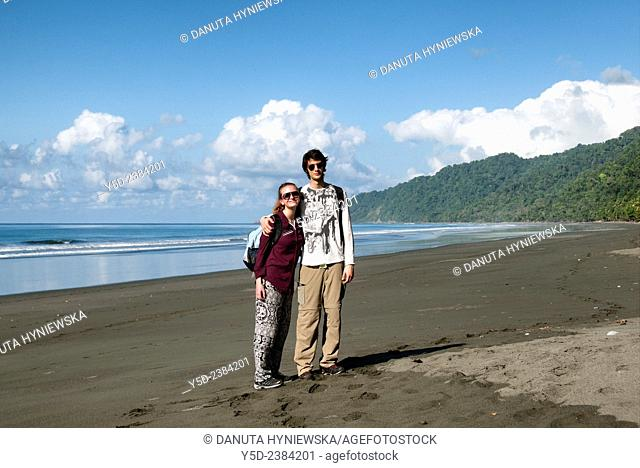 young travellers on empty beach, wild coast of the Pacific Ocean, Corcovado National Park, Costa Rica,