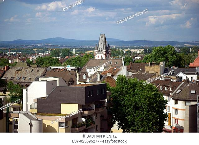 a view of apartment buildings and houses in the city of mainz with the tip of the iron tower