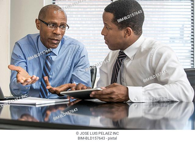Black businessmen working with digital tablet in office
