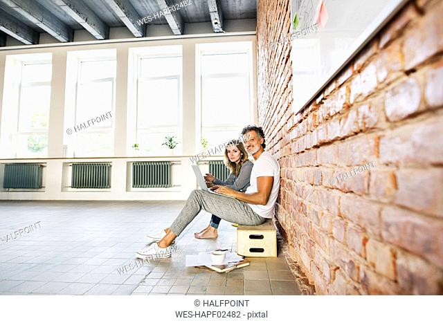 Businessman and woman sitting in a loft, using laptop, founding a start-up company