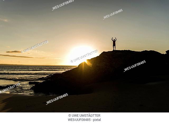 France, crozon peninsula, young man on rock at sunset